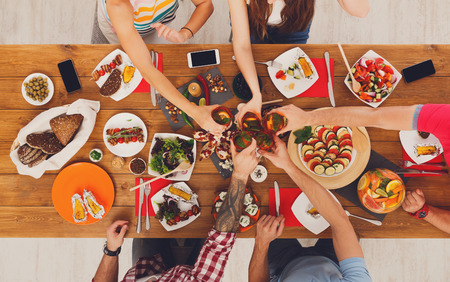 healthy meals: People clink glasses, saying cheers, eat healthy meals at party dinner table. Friends celebrate with organic food, ratatoille and corn barbecue on wooden table top view. Stock Photo
