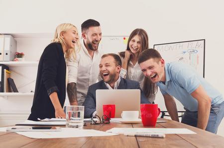 reir: Hombres de negocios felices ríen cerca de la computadora portátil en la oficina. El éxito de equipo corporativo de broma compañeros de trabajo femenina y masculina y divertirse juntos en el trabajo