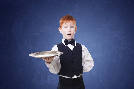 servant: Little waiter stands with empty tray serving. Smiling redhead child boy in suit plays restaurant servant at blue background Stock Photo