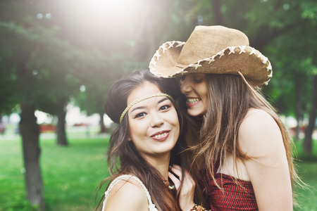 chic woman: Two happy young girls in boho chic style clothes. Female friends embracing, laughing and excited. Woman friendship, walk in the park outdoors
