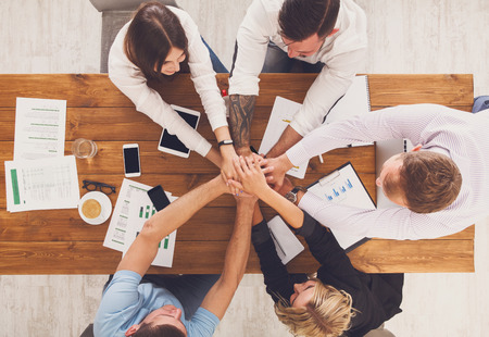 teambuilding: Team put hands together, show connection and alliance, top view of working table. Teambuilding in office, young businessmen and women in casual unite hands for teamwork and cooperation at new project. Stock Photo