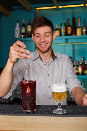 near beer: Barman in bar interior making alcohol berry cocktail. Professional bartender at work in bar mixing drink with ice in big glass and a beer portion stands near. Party time in night club