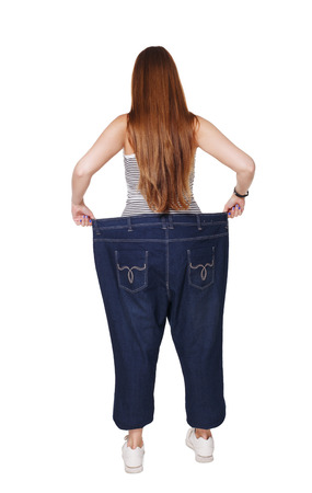 weight loss success: Young happy woman delighted with diet results, isolated on white. Girl celebrates weight loss success showing big size jeans on her slim figure. Good shape, healthy lifestyle and eating right concept.