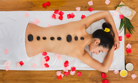 warming therapy: Black marble stone massage in spa. Top view of beautiful girl with stones on back and rose petals in wellness center. Pretty woman relaxation procedure, attractive young indian girl in beauty parlor.