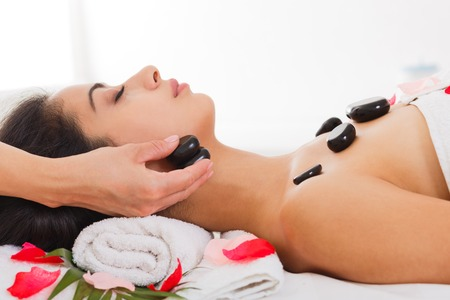 warming therapy: Black marble stone massage in spa. Female beautician doctor with patient in wellness center. Professional cosmetologist make relaxation procedure to beautiful indian girl in beauty parlor. Stock Photo