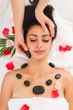 massagist: Black marble stone massage in spa. Female patient in wellness center. Professional massagist make relaxation procedure to beautiful indian girl in beauty parlor, top view with rose petals Stock Photo