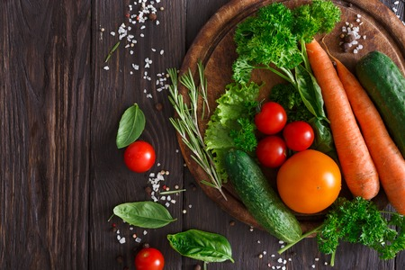 abundance: Desk with fresh organic vegetables on wood background. Healthy natural food abundance on rustic wooden table with copy space. Tomato, cucumber, carrot and other cooking ingredients top view Stock Photo