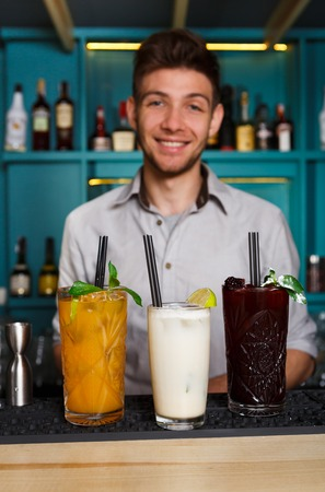 adding: Young handsome Barman offers exotic sweet alcohol cocktails in night club. Professional male bartender at work in bar made drinks for party. Focused on glasses with straws