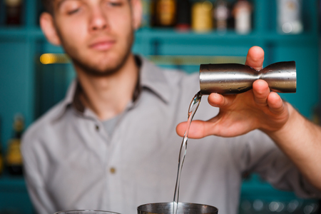 shot: Barmans hands in bar interior making alcohol shot cocktail. Professional bartender at work in bar pouring drink into measuring glass. Party time in night club. Service industry occupation Stock Photo