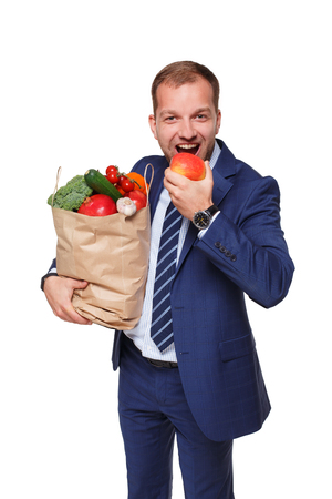 apple paper bag: Handsome young businessman in suit holds shopping bag full of groceries and eats apple, isolated at white background. Healthy food shopping. Paper package with vegetables and fruits, happy male buyer.
