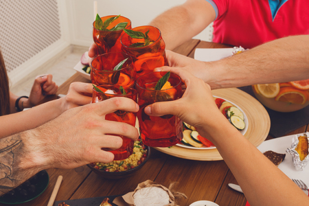 clink: Group of peoples hands closeup clink cocktail glasses, saying cheers at party dinner table in cafe or restaurant or at home. Friends company celebrate indoors.