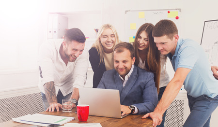internet site: Happy smiling business people looking at laptop screen in the office. Successful corporate team of female and male coworkers check internet site of company together, partners and colleagues. Stock Photo