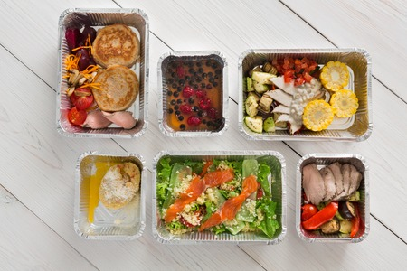 ration: Healthy food delivery, daily ration. Take away of natural organic low carb diet of vegetables and meat. Fitness nutrition in foil boxes. Top view, flat lay with copy space at white wood