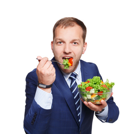 eat right: Healthy food and diet concept. Young businessman holds and eats fresh vegetable salad meal isolated on white background. Modern dieting and weight loss nutrition for busy men.
