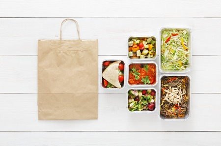 low carb diet: Healthy food delivery. Take away of natural organic low carb diet. Fitness nutrition in foil boxes, cutlery and brown paper package bag. Top view, flat lay with copy space at white wood