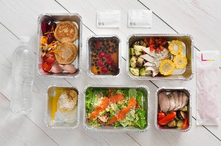 low carb diet: Healthy food delivery, daily ration. Take away of natural organic low carb diet. Fitness nutrition with water bottle in foil boxes. Top view, flat lay at white wood