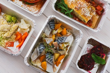 ration: Healthy food delivery, daily ration. Take away of natural organic low carb diet. Fitness nutrition in foil boxes. Top view, flat lay with copy space at white wood. Mackerel fish, vegetables and fruits Stock Photo