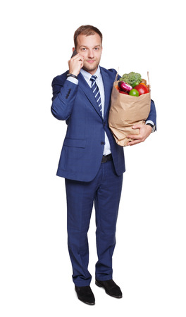 hurrying: Smiling young businessman calls mobile phone with shopping paper bag with groceries, vegetables and fruits, isolated at white background. Healthy food shopping. Full length portrait of hurrying buyer