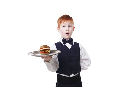 servant: Little suprised waiter stands with tray serving hamburger. Redhead child boy in suit plays restaurant servant isolated at white background