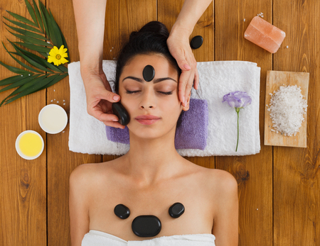 massagist: Black marble stone face massage in aroma spa. Beautician with female patient in wellness center. Professional therapy, relaxation procedure to beautiful indian girl in beauty parlor, top view on wood