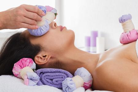 Herbal bola de la cara de masaje en el spa ayurveda. masajista de sexo femenino con la mujer joven en el centro de bienestar. La terapia de la salud a la hermosa muchacha india en un salón de belleza, vista lateral de la cara con los ojos cerrados