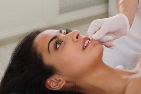 neuromuscular: Intra oral neuromuscular massage in spa. Female doctor with patient in wellness center. Professional cosmetologist make procedure to beautiful indian girl in cosmetology cabinet or beauty parlor.
