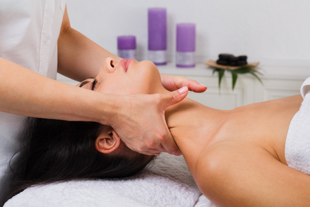 cosmetologist: Unrecognizable female beautician doctor with patient in spa wellness center. Professional cosmetologist make body neck massage to beautiful indian girl in cosmetology cabinet or beauty parlor. Stock Photo