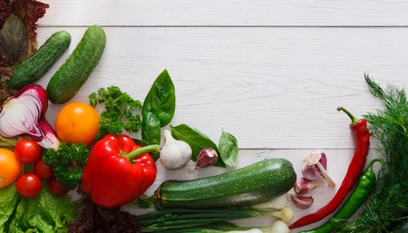 market bottom: Bottom line border on white wood for menu or recipe, fresh organic tasty vegetables and greens background. Healthy natural food on wooden table with copy space. Bright cooking ingredients top view