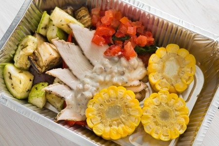carb: Healthy food delivery or take away, diet concept. Organic nutrition with protein, carb and fat balance. Weight loss dish in foil box. Vegetables, turkey and corn.