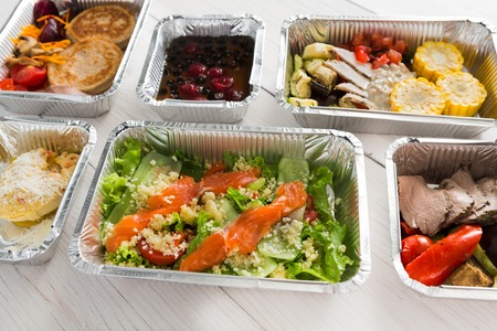 low fat diet: Healthy food delivery, daily ration. Take away low fat diet meals of vegetables, fruits, fish and meat. Fitness nutrition in foil boxes on white wood background. Proper protein and carb balance