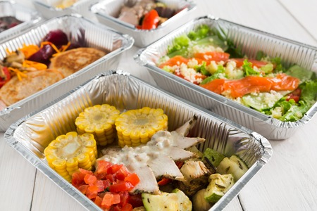 carb: Healthy food delivery, daily ration. Take away of natural organic low carb diet of vegetables, fish and meat. Fitness nutrition in foil boxes on white wood background