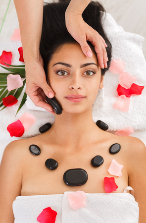 massagist: Black marble stone massage in spa. Female patient in wellness center. Professional massagist make relaxation procedure to beautiful indian girl in beauty parlor, top view on face, bed of rose petals