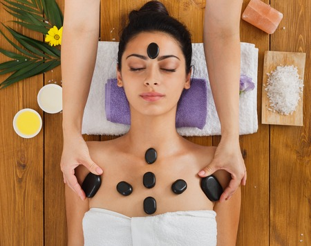 massagist: Black marble stone massage in spa. Beautician with female patient in wellness center. Professional cosmetologist make relaxation procedure to beautiful indian girl in beauty parlor, top view on wood
