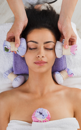 massagist: Herbal ball face massage in ayurveda spa. Female massagist with young woman in wellness center. Healthcare therapy to beautiful indian girl in beauty parlor, top view of face with eyes closed Stock Photo