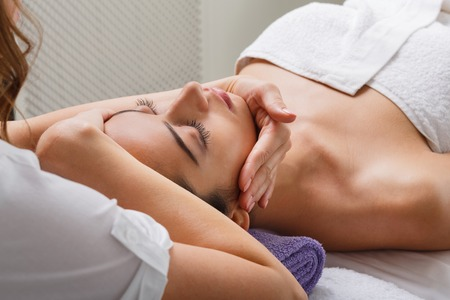 cosmetologist: Head and face massage in spa. Female beautician doctor with patient in wellness center. Professional cosmetologist make procedure to beautiful indian girl in cosmetology cabinet or beauty parlor. Stock Photo