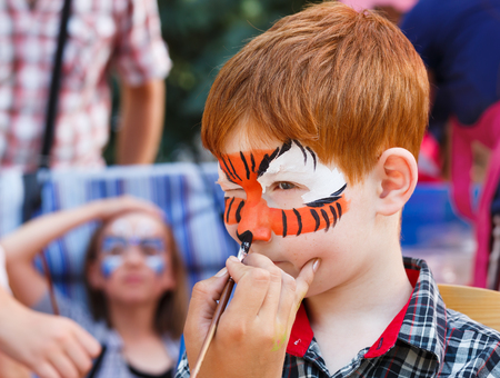 Child animator, artists hand draws face painting to little boy. Child with funny face painting. Painter makes tiger eyes on boys face. Children holiday, event, birthday party, entertainment.