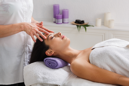Head relaxing massage in spa. Female beautician doctor with patient in wellness center. Professional cosmetologist make procedure to beautiful indian girl in cosmetology cabinet or beauty parlor. Banque d'images