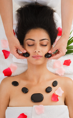 massagist: Black marble stone face massage in spa. Female patient in wellness center. Professional massagist make relaxation procedure to beautiful indian girl in beauty parlor, top view with rose petals Stock Photo