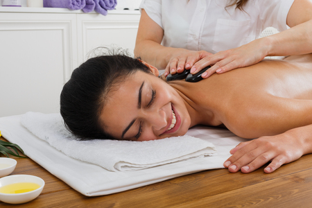 massagist: Black marble stone back massage in spa. Female beautician doctor with patient in wellness center. Professional massagist make relaxation procedure to beautiful indian girl in beauty parlor.