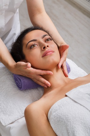 cosmetologist: Head massage in spa. Female beautician doctor with patient in wellness center. Professional cosmetologist make face procedure to beautiful indian girl in cosmetology cabinet or beauty parlor. Stock Photo