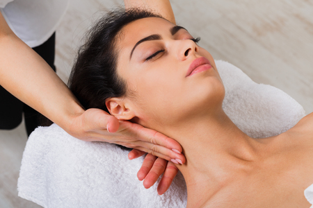 Unrecognizable female beautician doctor with patient in spa wellness center. Professional cosmetologist make body neck massage to beautiful indian girl in cosmetology cabinet or beauty parlor. Stock Photo