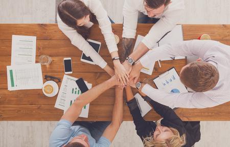 Team setzen die Hände zusammen, der Verbindungs ??und Allianz, Draufsicht auf Arbeitstisch. Teambuilding im Büro, junge Unternehmer und Frauen in ungezwungener vereinen Hände für Teamarbeit und Kooperation bei neuen Projekt.