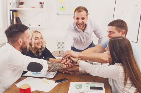 teambuilding: Team put hands together, show connection and alliance. Teambuilding in office, young happy businessmen and women in casual unite hands for teamwork and cooperation at new project.