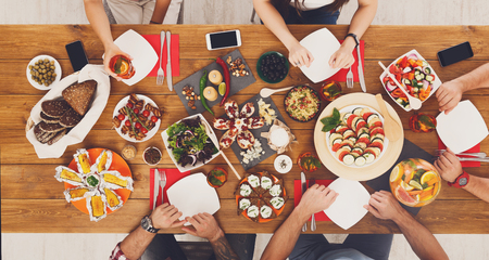 People eat healthy meals with non-alcoholic cocktails at festive table served for party. Friends celebrate with organic food on wooden table top view. Stock Photo