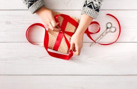 DIY Hobby. Hände der Frau Einwickeln Weihnachten oder anderen Urlaub handgefertigt in Papier mit rotem Band. Machen Bogen gegenwärtig Box, Dekoration von Geschenk. Schere auf weißen Holztisch, Ansicht von oben.