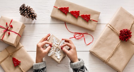 Creative hobby. Womans hands wrap christmas holiday handmade present in craft paper with twine ribbon. Making bow at xmas gift box, decorated with snowflake on white wooden table, top view.