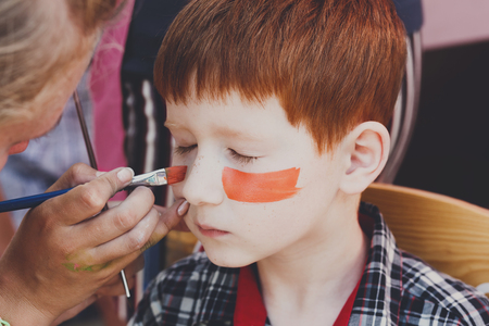 tiger eyes: Child animator, artists hand draws face painting to little boy. Child with funny face painting. Painter makes tiger eyes on boys face. Children holiday, event, birthday party, entertainment.