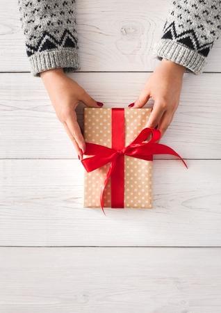 Manos de la mujer dan envueltos de la Navidad u otro día de fiesta hecha a mano presente en papel con cinta roja. caja de regalo, decoración y de regalo en la mesa de madera blanca, vista desde arriba, con copia espacio, vertical Foto de archivo