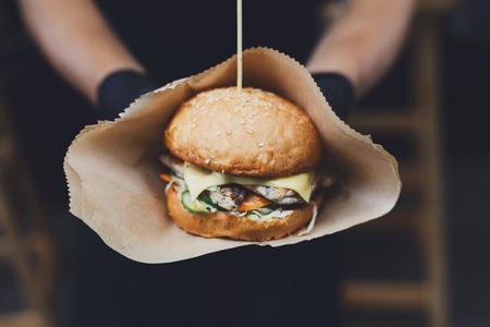 Frische Burger am Grill zubereitet draußen in Kraftpapier. COOKOUT amerikanische BBQ Essen. Großer Hamburger mit Steak Fleisch und Gemüse Nahaufnahme mit Koch unkonzentriert im Hintergrund. Street Food, Fast Food. Lizenzfreie Bilder