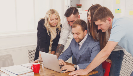internet site: Business people group portrait look attentive at laptop in the office. Successful corporate team of female and male coworkers check internet site of company together, partners and colleagues.